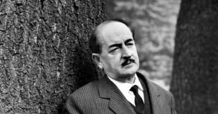 (PREMIUM RATES APPLY) The Italian poet Salvatore Quasimodo, elegantly dressed with jacket and tie, with a melancholic expression, is leaning against the trunk of a big tree in Parco Sempione. Milan (Italy), 1962. (Photo by Mario De Biasi/Mondadori Portfolio via Getty Images)